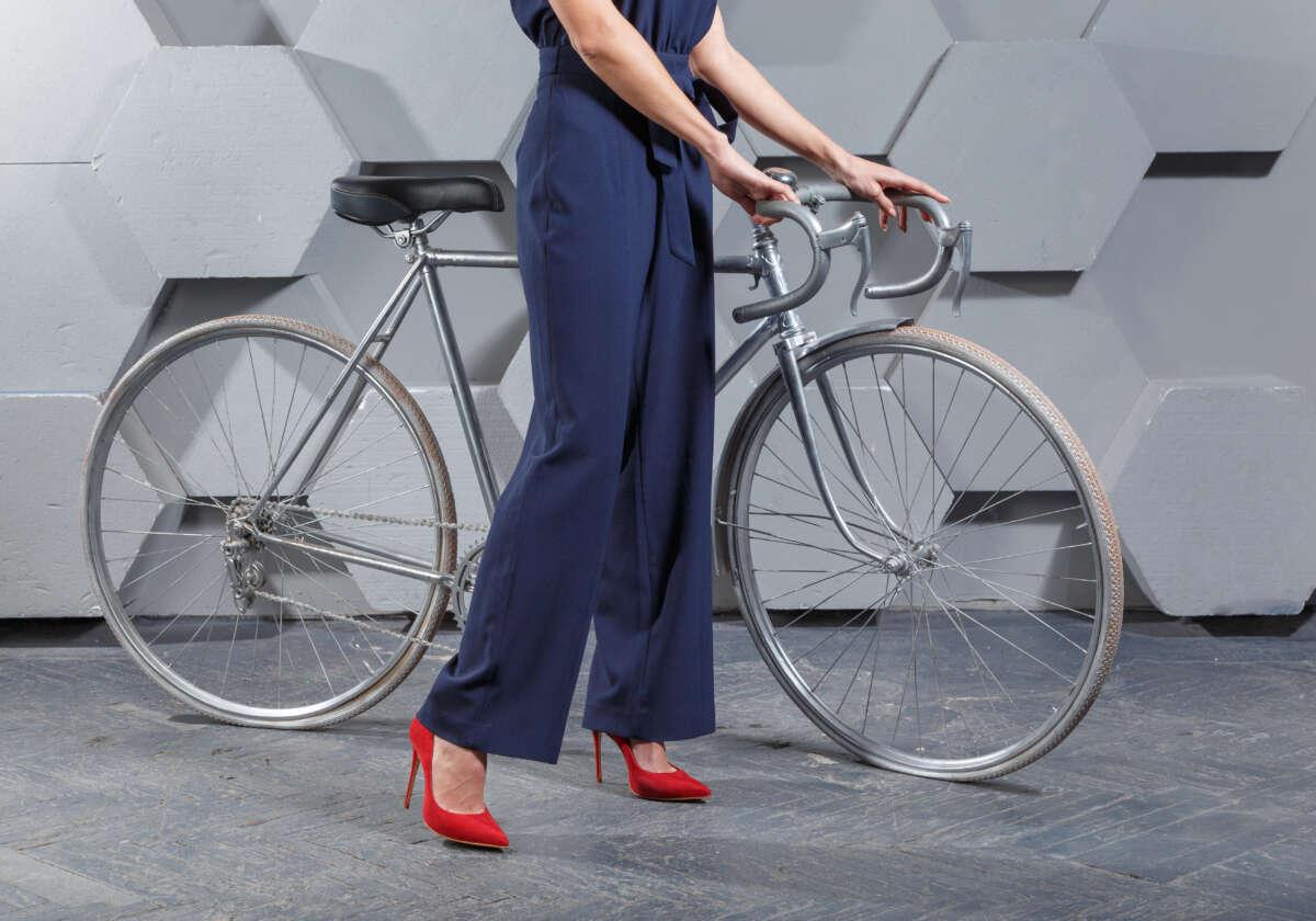 kobieta w czerwonych szpilkach przy rowerze
