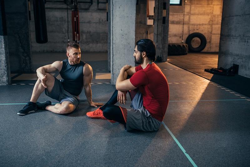 Dwaj muskularni mężczyźni siedzą na podłodze na siłowni